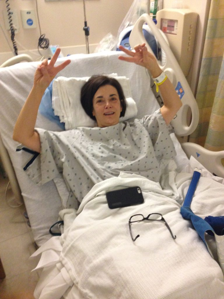 Pre operation prep for shoulder surgery, giving peace sign with both hands.